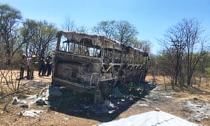 Firefighters examine the charred remains of a bus in Gwanda, Zimbabwe.