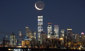 A crescent moon rises before sunrise above lower Manhattan and One World Trade Center in New York City