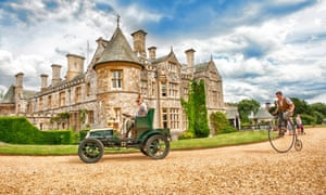 Exhibits from the National Motor Museum Beaulieu. A 1920s motor car is pursued by a man on a penny farthing in front of the Montagu family mansion.