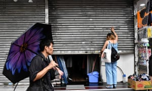A woman closes her shop before a protest march in Central district, Hong Kong