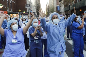 Nurses and medical workers react as police officers and pedestrians cheer them outside Lenox Hill hospital in New York in April.