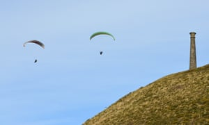 Paragliders beat across the seaward face of Pen Dinas