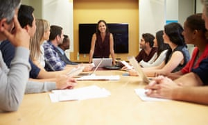 A woman addresses a boardroom meeting