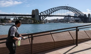 A worker disinfects hand rails in Sydney, Australia, May 20, 2020.