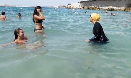 Woman bathes wearing a burkini