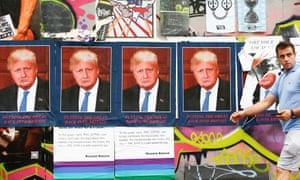 A man walks past posters merging photographs of Donald Trump and Boris Johnson