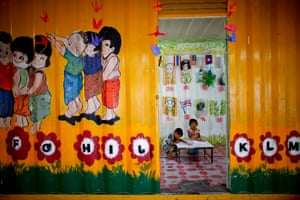 Paij and Sok Jia from Cambodia, both three years old, make drawings inside a shipping container-turned-school