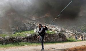 A Palestinian demonstrator hurls stones at Israeli troops during a protest against Jewish settlements.