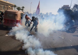 Baghdad, Iraq A protester grabs a teargas canister fired by riot police amid clashes following anti-government demonstrations in al-Khillani Square