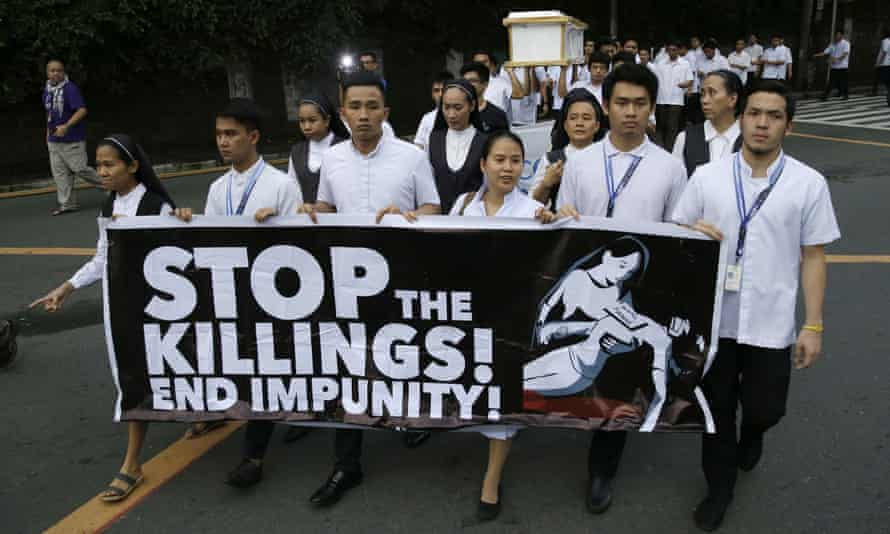seminarians and nuns carry slogans and a mock coffin during a rally in Manila, Philippines, against drug-related killings and martial law