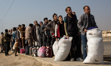 Men wait to go through and ID and security check at a civilian screening point after fleeing Mosul in Gogjali, Iraq.