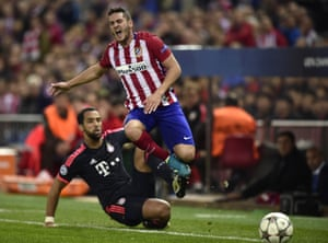Bayern Munich's Medhi Benatia takes out Atletico Madrid's Koke and gets a yellow card for his troubles.