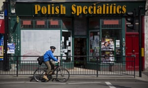 A man cycles past a Polish Specialities shop in London.