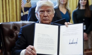 Donald Trump displays one of five executive orders he signed related to the oil pipeline industry in the oval office of the White House January 24, 2017 in Washington, DC.