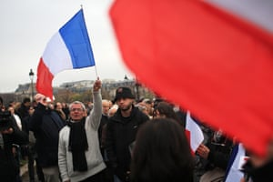 People holding French flags gather outside the Invalides, during a ceremony honouring those killed