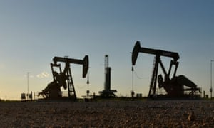 Pump jacks operate in front of a drilling rig in an oilfield in Midland, Texas