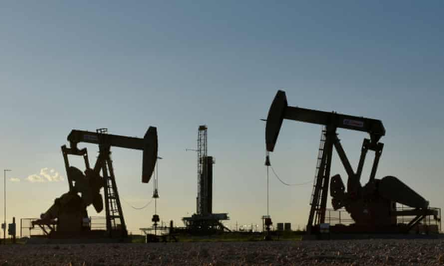 Pump jacks operate in front of a drilling rig in an oil field in Midland, Texas