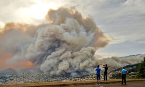 People take pictures of the smoke rising from a wildfire at Curral dos Romeiros in Funchal.