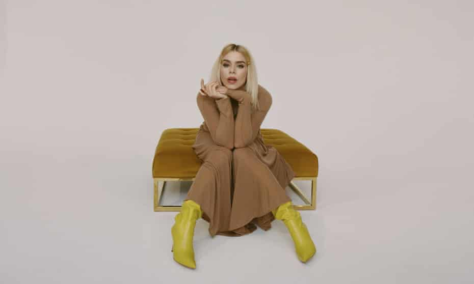 Billie Piper sitting on a rich velvet stool wearing a brown dress and bright yellow leather boots