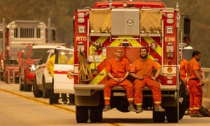 Inmate firefighters sit on the back of a fire truck while taking a break from the Bear fire, in unincorporated Butte county, in Oroville, California.