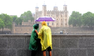 two tourists shelter under a brolly across the river form the Tower of London