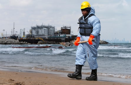 An oil-spill response contractor cleans up crude oil on a beach after a BP oil spill on Lake Michigan in Whiting, Indiana, US.