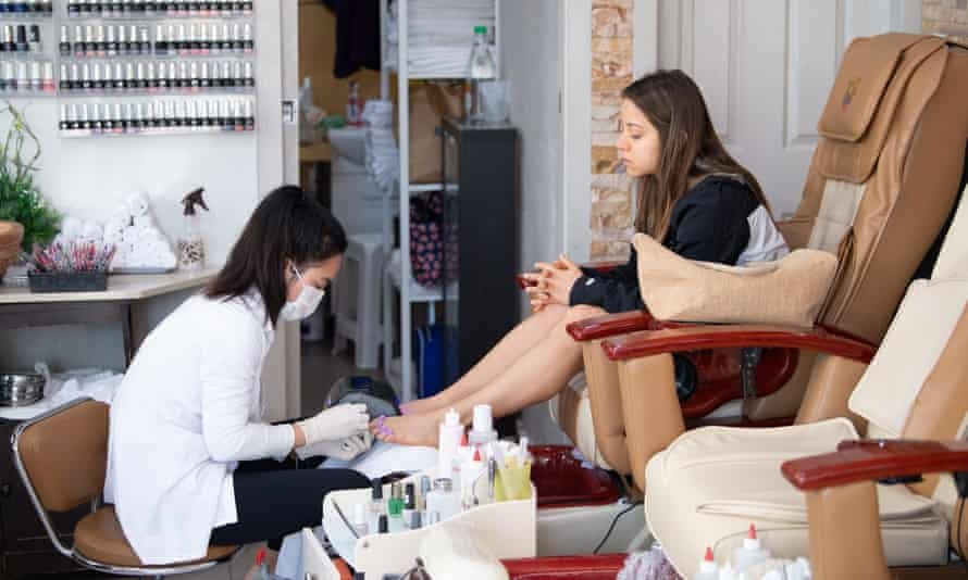 A technician works on a customer's feet at a nail parlour in Sydney on Monday on the first day beauty salons were allowed to open again in NSW.