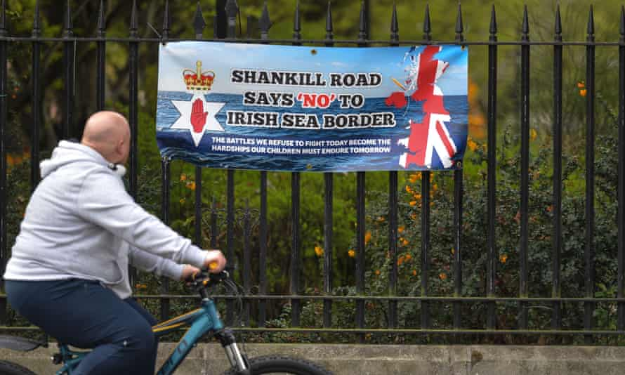 A cyclist passes a banner protesting against the Northern Ireland protocol on Belfast's Shankill Road