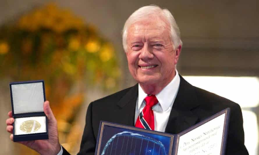 Former US president Jimmy Carter shows off his 2002 Nobel peace prize, joining three other US presidential winners.