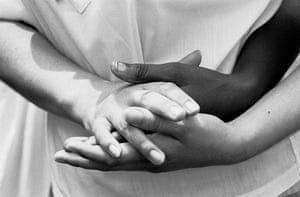 In summer 1964, a volunteer from the civil rights group the Student Nonviolent Coordinating Committee clasps hands with one of her students at a Freedom School created for African Americans in Valley View
