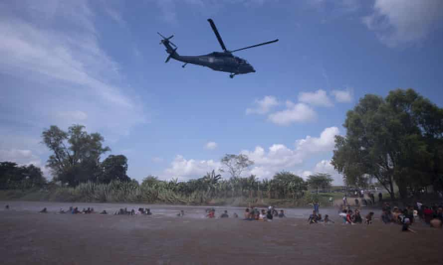 A Mexican federal police helicopter flies close to the Suchiate river that connects Mexico and Guatemala, in order to create a downwash force to discourage a new group of Central American migrants wading across the river on Monday.