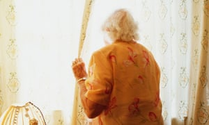 An elderly woman looks out from her home.