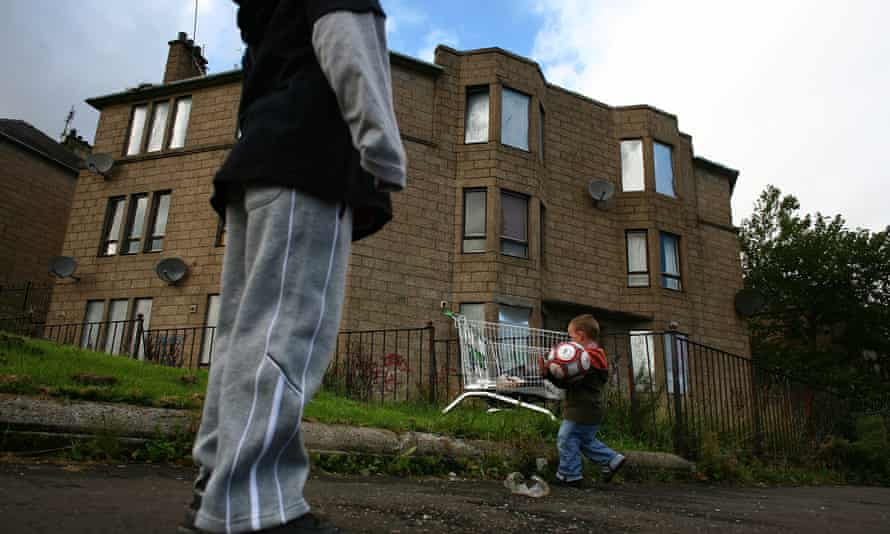 Boys play football in a run down street with boarded up houses
