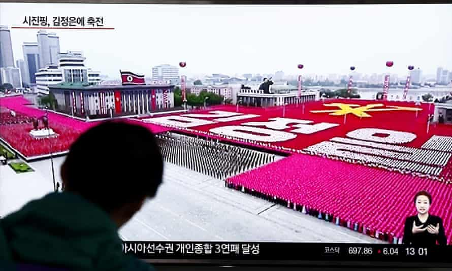 South Koreans watch the North Korean congress parade on TV.