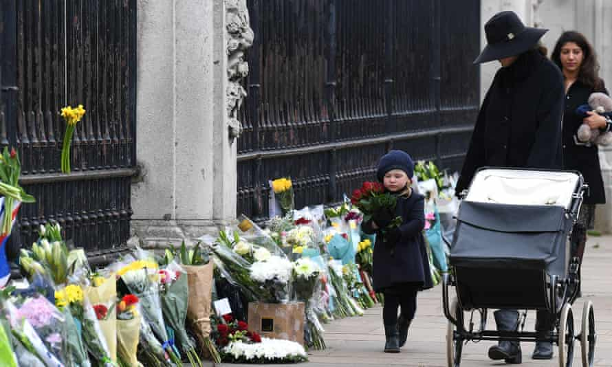 A girl carries flowers to lay as a tribute to Prince Philip outside Buckingham Palace.