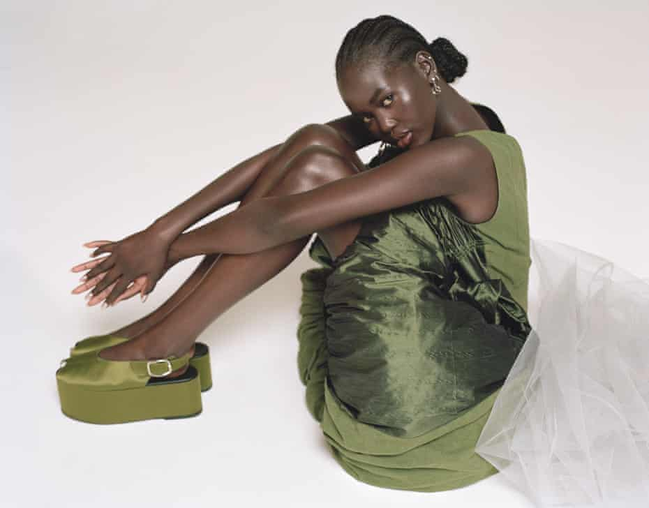 'I want to see real change': Adut Akech wears green dress by loewe.com and flatforms by erdem.com. All jewellery by Vintage Mercedes-Benz.