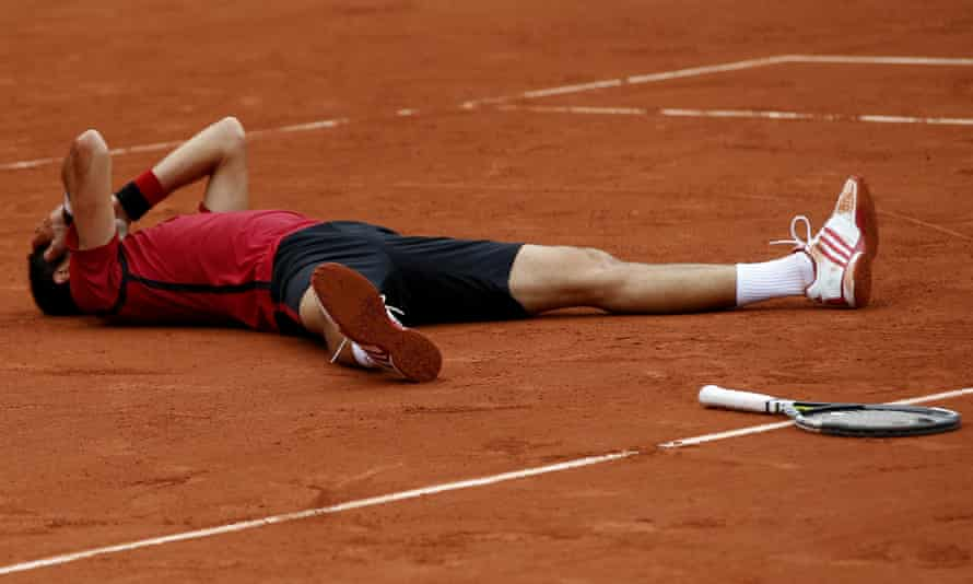 Djokovic falls to the ground after clinching the title and a career grand slam.