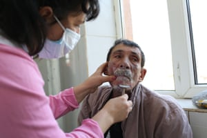 """Andrei, 44, has his beard trimmed by a nurse at Leamna sanatorium in Craiova, Romania. Andrei was diagnosed with HIV and TB two months before this photo was taken after police found him coughing up blood on the streets. The Romanian Government provides no extra support for TB patients beyond one year of sick leave, which only a handful of patients receive. The unemployed, agricultural workers and those working """"off the books"""" are forced to make the impossible decision of completing an arduous treatment regime, or providing for their family. The majority chooses the latter."""