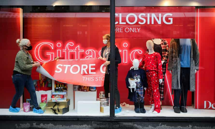 Staff attach a closing-down sign in a window of Debenhams store in Manchester