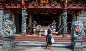 A worker sprays disinfectant at Kwan Te Kong temple in Palembang, South Sumatra province, Indonesia