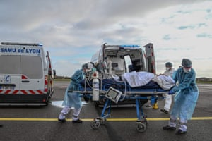 Lyon, FranceMedical staff transport a patient on a stretcher to a waiting medical flight at Bron airport during the Covid-19 pandemic.