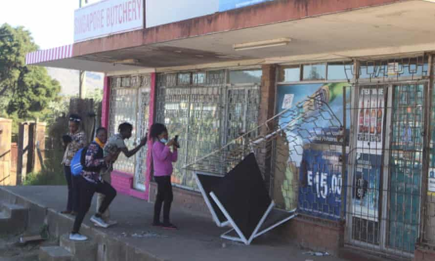 People take pictures of a damaged shop in Mbabane, Eswatini, following protests.