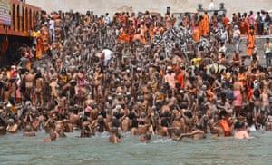 Uttarakhand, India. Holy men take the holy dip in Ganga river during the Kumbh Mela royal bath