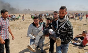Palestinians carry a demonstrator injured during clashes with Israeli forces near the border between the Gaza strip and Israel