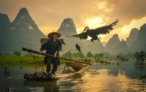 A Guilin cormorant tossed into the air by the fisherman dives into the river Li