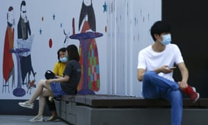 People wearing face masks as a precaution against coronavirus rest on the bench during a launch break outside an office building in Beijing, Thursday, 23 July 2020.