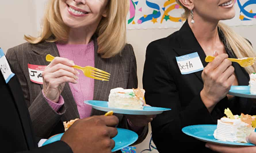 Four office workers eating cake