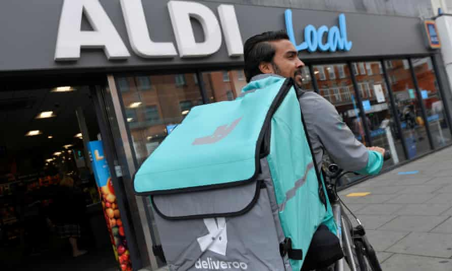 A Deliveroo delivery rider with a bag of Aldi groceries in London.