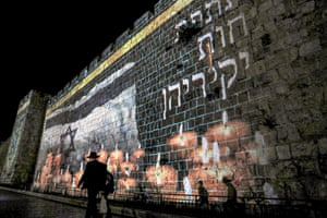 Jerusalem. A projection of lit candles is displayed on the old city walls as part of a national day of mourning for victims of the disaster at Mount Meron