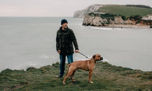 Daniel Payne stands with his dog Drago on the coastal path overlooking Freshwater Bay.